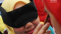 Penampilan peserta saat merias wajah dengan mata tertutup di Kantor Balai Kota Tangerang Selatan, Banten, Jumat (27/4). Perlombaan ini sekaligus bertujuan meningkatkan kualitas hidup perempuan. (Merdeka.com/Arie Basuki)