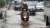 Pengendara motor mencoba menerobos genangan air di Jalan Cikini Raya, Jakarta, Sabtu (7/11). Meski baru pertama kali diguyur hujan selama musim kemarau, jalan tersebut langsung terendam air. (Liputan6.com/ Immanuel Antonius)