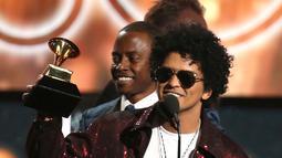 Penyanyi R&B, Bruno Mars mengangkat trofi Song of The Year pada ajang Grammy Awards 2018 di New York City, Minggu (28/1). Tak kurang dari 6 piala Grammy berhasil dibawa pulang termasuk song of the year untuk That's What I Like. (Matt Sayles/Invision/AP)