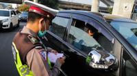Polisi menilang kendaraan saat pemberlakuan perluasan sistem ganjil genap di kawasan Jalan Fatmawati Raya, Jakarta, Senin (9/9/2019). Pada masa uji coba, polisi hanya melakukan upaya preventif seperti sosialisasi kepada pelanggar. (Liputan6.com/Faizal Fanani)