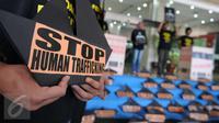 Poster bertuliskan Stop Human Trafficking' saat aksi protes di depan Kemenaker, Jakarta, Jumat (9/12). Sejumlah aktivis mendesak Pemerintah memperbaiki kebijakan penempatan buruh migran anak buah kapal asing di luar negeri. (Liputan6.com/Helmi Afandi)
