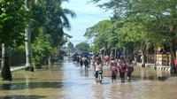 Anak sekolah melintasi genangan banjir di Sidareja, Cilacap, Jawa Tengah. (Foto: Liputan6.com/Muhamad Ridlo)