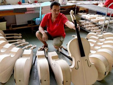 Pekerja memeriksa selo di sebuah bengkel kerja di Queshan, Provinsi Henan, China, Rabu (20/5/2020). Kawasan industri penghasil alat musik tersebut mampu memproduksi 30.000 biola dan selo setiap tahun. (Xinhua/Zhu Xiang)