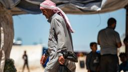 Seorang pria Suriah yang terlantar membawa seekor ayam dalam sebuah tas kembali ke tendanya belanjaan selama bulan suci Ramadan di kamp Washukanni untuk para pengungsi internal di provinsi Hasakeh di timur laut Suriah, (10/5/2020). (AFP/Delil Souleiman)