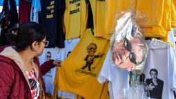 Seorang wanita melihat kaus bergambar Capres Brasil, Jair Bolsonaro dari sayap kanan di sebuah toko pinggir jalan yang populer di Sao Paulo, 8 Oktober 2018. Bolsonaro unggul dalam penghitungan suara pemilu putaran pertama. (AFP/NELSON ALMEIDA)