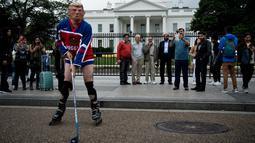 Wisatawan melihat seorang pria mengenakan topeng Presiden AS Donald Trump dan kostum tim hoki Rusia saat unjuk rasa di luar Gedung Putih di Pennsylvania Avenue di Washington, DC, (29/10). (AFP Photo/Brendan Smialowski)