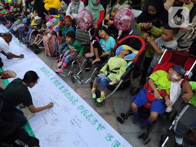Masyarakat dan relawan menandatangani spanduk saat memperingati Hari Cerebral Palsy Sedunia di area Car Free Day, Jakarta, Minggu (13/10/2019). Peringatan yang jatuh 6 Oktober itu dimanfaatkan untuk mensosialisasikan dan menggalang kepedulian bagi penyandang cerebral palsy (Liputan6.com/Johan Tallo)
