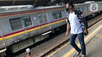Calon penumpang melintasi rangkaian KRL Commuter Line di Stasiun Depok Baru, Jawa Barat, Senin (25/5/2020). Banyaknya warga yang silaturahmi selama lebaran menyebabkan perjalanan KRL tetap dipadati penumpang, meskipun waktu operasional dibatasi. (Liputan6.com/Immanuel Antonius)