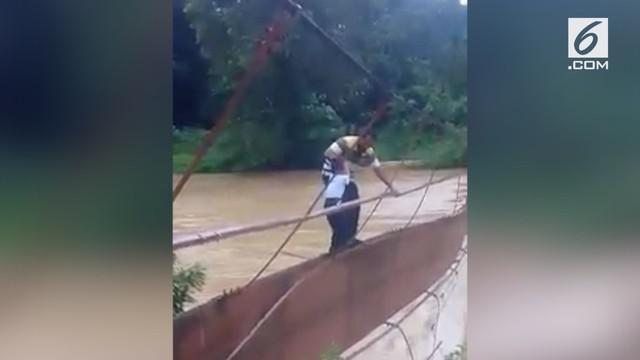 Agar dapat pergi ke sekolah. Ayah ini mengantarkan anaknya ke sekolah dengan melewati jembatan yang hampir putus.