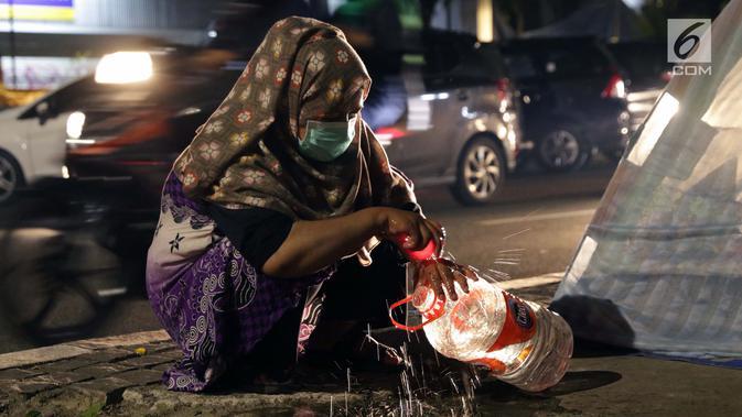 Pencari suaka mencuci tangan jelang masuk ke dalam tenda yang dibangun di atas trotoar depan kantor UNHCR, Jalan Kebon Sirih, Jakarta, Jumat (5/7/2019). Para pencari suaka ini membangun tenda-tenda dan meminta kepastian perlindungan dari UNHCR . (/Helmi Fithriansyah)