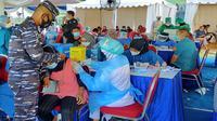 Seorang personel TNI AL menenangkan salah satu peserta vaksinasi Covid-19 yang takut disuntik di acara serbuan vaksin secara massal di Stadion Gajayana, Kota Malang, pada Sabtu, 7 Agustus 2021 (Liputan6.com/Zainul Arifin)