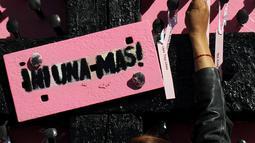 Aksi seorang ibu dan aktivis menempatkan nama-nama wanita yang dibunuh di Ciudad Juarez pada sebuah salib hitam di Jembatan Internasional Paso del Norte, Ciudad Juarez, Chihuahua, Meksiko, Rabu (7/3). (HERIKA MARTINEZ/AFP)