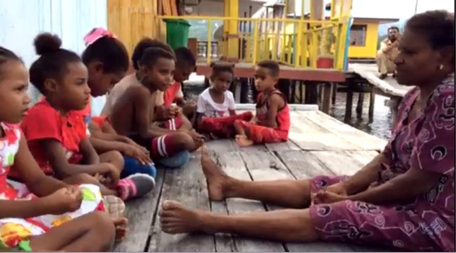 Seorang nenek asal Papua, Nene Adri Meraudje (62), mengajari bahasa daerah kepada anak-anak setempat, Kampung Enggros, Jayapura. (Liputan6.com/Katharina Lita)