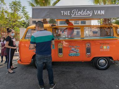 Emad Abdeljawwad menjual hot dog dan minuman dari mobil van yang telah diubah di Ramallah, Tepi Barat, 23 September 2020. Dengan sebagian besar restoran tutup karena pembatasan COVID-19, food truck telah memungkinkan pengusaha Palestina untuk menemukan cara tetap bekerja. (AP Photo/Nasser Nasser)