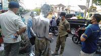 Petugas Satpol PP Kabupaten Rembang ketika menertibkan manusia perak di lampu traffic light Eks Stasiun Jl Kartini, Rembang.