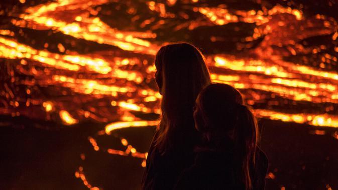 Orang-orang menyaksikan aliran lahar dari letusan gunung berapi di Semenanjung Reykjanes, barat daya Islandia, Senin (29/3/2021). Letusan gunung berapi tersebut tidak dipandang sebagai ancaman bagi kota-kota sekitar dan warga yang menyaksikan dari dekat. (AP Photo/Marco Di Marco)