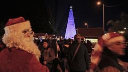 Pria berkostum Sinterklas terlihat sekitar pohon natal dari botol plastik di kota Chekka, Lebanon, 15 Desember 2019. Caroline Chaptini, yang mengorganisasi proyek ini menyebut, kreasi ini terjadi berkat kerjasama dengan pemerintah kota setempat. (Ibrahim CHALHOUB/AFP)
