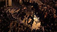 Pengunjuk rasa antipemerintah melempari polisi dengan pagar dalam protes menentang rencana pengenaan pajak baru di Beirut, Lebanon, Jumat (18/10/2019). Ribuan orang turun ke jalan melampiaskan kemarahannya kepada para politisi yang mereka tuduh korup dan salah urus negara. (AP Photo/Hassan Ammar)