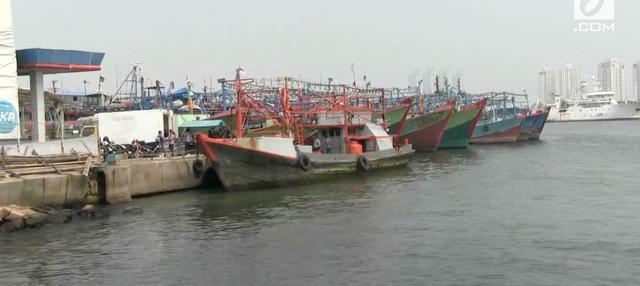 Gelombang tinggi dan cuaca buruk membuat nelayan di pelabuhan Muara Baru memilih menyandarkan perahunya dan tidak melaut.