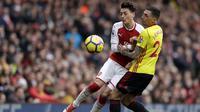 Gelandang Arsenal, Mesut Ozil, berebut bola dengan bek Watford, Jose Holebas, pada laga Preimer League di Stadion Emirates, Minggu (11/3/2018). Arsenal menang 3-0 atas Watford. (AP/Matt Dunham)