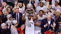 Pebasket Toronto Raptors, Kawhi Leonard, mengangkat trofi usai mengalahkan Milwaukee Bucks pada NBA Final Wilayah Timur di Scotiabank Arena, Toronto, Sabtu (25/5). Raptors menang 4-2 atas Bucks. (AFP/Claus Andersen)