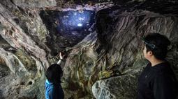 Arkeolog dari Departemen Seni Rupa di Ratchaburi melihat lukisan gua yang baru ditemukan di taman nasional Khao Sam Roi Yot di pesisir provinsi Prachuap Kiri Khan (10/9/2020). Ini merupakan penemuan menakjubkan bagi tim arkeolog Thailand. (AFP/Lillian Suwanrumpha)