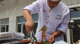 Seorang koki menyajikan makanan dengan patung mini mitos Pemanah Cina Houyi di Dezhou, Shandong Timur, Cina, 2 Agustus 2018. Koki memasak menggunakan kompor tenaga surya. (AP Foto/Fu Ting)
