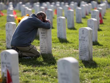 Chris Plank memegang nisan temannya Sersan Mayor Bradly Dean Conner saat peringatan Hari Veteran di Pemakaman Nasional Arlington, AS, Senin (11/11/2019). Rakyat AS memperingati Hari Veteran untuk menghormati mereka yang pernah bertugas di militer AS. (Alex Wong/Getty Images/AFP)