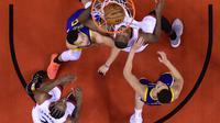 Pebasket Toronto Raptors, Serge Ibaka, berusaha memasukan bola saat melawan Golden State Warriors pada laga Final NBA di Scotiabank Arena, Toronto, Kamis (30/5). Raptors menang 118-109 atas Warriors. (AP/Nathan Denette)