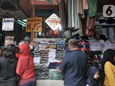 Pembeli memilih seragam sekolah di Pasar Jatinegara, Jakarta, Minggu (5/1/2020). Jelang hari pertama belajar di semester baru, warga terdampak banjir di Kampung Melayu dan sekitarnya terpaksa membeli seragam baru untuk anaknya akibat banjir yang merendam rumah mereka. (merdeka.com/Iqbal Nugroho)