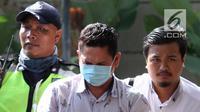 Kepala Kantor Imigrasi Kelas I Mataram Kurniadie (tengah) tiba di Gedung KPK, Jakarta, Selasa (28/5/2019). Kurniadie terjaring operasi tangkap tangan (OTT) KPK bersama tujuh orang lainnya. (Liputan6.com/HO/Joni)