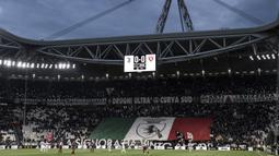 Suporter Juventus membentangkan bendera Italia raksasa saat melawan Torino pada laga Serie A di Stadion Allianz, Turin, Jumat (3/5). Kedua klub bermain imbang 1-1. (AFP/Marco Bertorello)