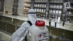Petugas PMI Jakarta menyemprotkan cairan disinfektan di Masjid Istiqlal, Jakarta, Jumat (16/4/2021). Kegiatan tersebut dilakukan untuk memberikan rasa nyaman bagi jemaah saat menjalankan ibadah di bulan suci Ramadhan dan menghindari penyebaran COVID-19. (Liputan6.com/Faizal Fanani)
