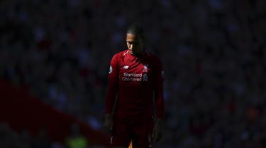 Bek Liverpool, Virgil van Dijk, tampak lesu usai gagal meraih gelar juara Premier League di Stadion Anfield, Minggu (12/5). Liverpool menyudahi musim ini di peringkat kedua klasemen Premier League dengan nilai 97. (AP/Dave Thompson)