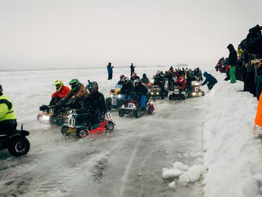 Peserta berkompetisi dalam kejuaran balap mesin potong rumput tahunan di Lavia, Finlandia, 9 Februari 2019. Para pembalap harus menyelesaikan sebanyak mungkin putaran di area pertandingan yang tertutup salju. (Alessandro RAMPAZZO/AFP)