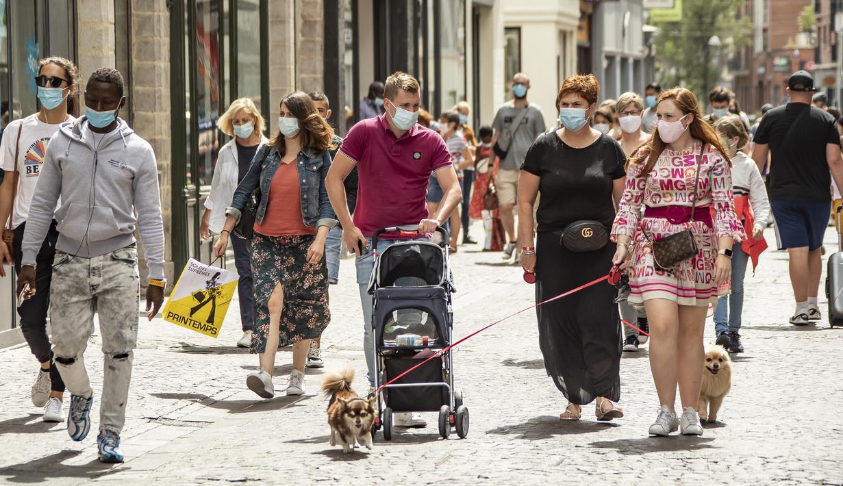 Sejumlah warga yang mengenakan masker melintasi jalan di pusat Kota Lille, Prancis, Senin (3/8/2020). Otoritas Prancis memerintahkan warga untuk mengenakan masker di tempat umum outdoor saat penyebaran COVID-19 semakin cepat dan jumlah pasien kembali melonjak. (Xinhua/Sebastien Courdji)