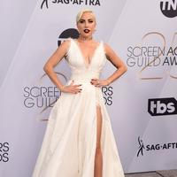 Lady Gaga berpose saat menghadiri acara 25th Screen Actors Guild Awards di Los Angeles, California, AS (28/1). Lady Gaga tampil anggun menggenakan gaun putih dengan belahan hingga paha kreasi Dior Haute Couture. (AP Photo/Jordan Strauss)