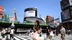 Seorang wanita menggunakan payung untuk melindungi dirinya dari sinar matahari selama gelombang panas saat melintasi jalan di distrik Shinjuku Tokyo, Minggu (4/8/2019). Setelah menyerang beberapa wilayah di Eropa, suhu tinggi juga terjadi di Jepang. (Charly TRIBALLEAU / AFP)