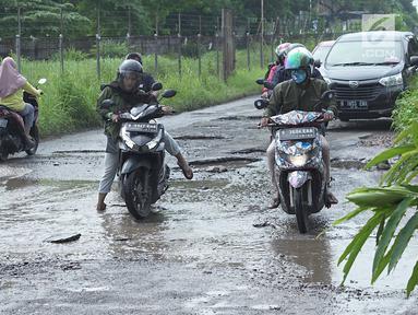 Pengendara motor berusaha menghindari jalan rusak yang menjadi kubangan air di Jalan Raya Gas Alam, Depok, Jawa Barat, Selasa (7/5). Kondisi jalan yang tidak kunjung diperbaiki tersebut menjadi kubangan air setiap hujan serta berbahaya bagi keselamatan pengguna jalan (Liputan6.com/Immanuel Antonius)