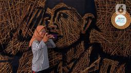 Pengunjung berswafoto di depan karya instalasi bambu berbentuk wajah Jenderal Sudirman karya Nus Salomo yang dipamerkan pada aksi Kenali Sejarah Raihlah Mimpimu di Terowongan Dukuh Atas, Jakarta, Minggu (24/11/2019). (Liputan6.com/Johan Tallo)