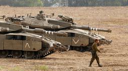 Tentara Israel berjalan melewati tank di dekat perbatasan Gaza-Israel, Jumat (19/10). Pengerahan itu disebut menjadi yang terbesar sejak perang 2014. (JACK GUEZ/AFP)