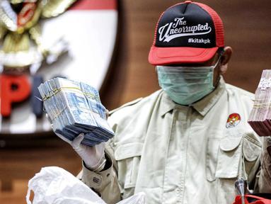 Penyidik menunjukkan barang bukti OTT Bupati Lampung Selatan Zainudin Hasan berupa uang senilai Rp 600 juta. di Gedung KPK, Jumat (27/7). Zainudin ditetapkan sebagai tersangka dugaan suap proyek infrastruktur. (Liputan6.com/Faizal Fanani)