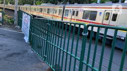 Kereta melintas di perlintasan sebidang dekat Stasiun Palmerah dan Gedung DPR/MPR yang ditutup permanen di Jakarta, Selasa (1/12/2020). Perlintasan ini tengah dilakukan kajian apakah di lokasi itu memungkinkan pembangunan flyover atau underpass. (Liputan6.com/Immanuel Antonius)