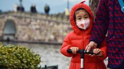 Seorang anak saat mengunjungi kawasan Danau Barat yang indah di Hangzhou, Provinsi Zhejiang, China timur (19/2/2020). Taman-taman dan objek wisata yang tergabung dalam kawasan Danau Barat telah dibuka kembali secara teratur pada Rabu (19/2). (Xinhua/Zheng Mengyu)