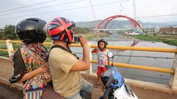 Seorang anak berpose dengan latar Jembatan Kali Kuto di ruas tol fungsional Batang-Semarang, Gringsing, Jateng, Rabu (13/6). Berfungsinya Jembatan ini akan memperlancar arus mudik dan arus balik Lebaran 2018. (Liputan6.com/Arya Manggala)