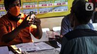 Petugas memotret warga penerima bantuan sosial (bansos) di kawasan Kedoya Selatan, Jakarta Barat, Rabu (28/7/2021). Selain bansos dari APBD DKI Jakarta, sekitar 738 ribu orang lainnya mendapatkan bantuan yang disalurkan oleh pemerintah pusat melalui Kementerian Sosial. (Liputan6.com/Johan Tallo)
