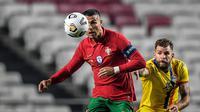 Pemain depan timnas Portugal, Cristiano Ronaldo (kiri) berebut bola dengan gelandang timnas Andorra, Moises San Nicolas dalam pertandingan uji coba internasional di Estadio da Luz, Kamis (12/11/2020) dini hari WIB. Portugal menang 7-0 atas tamunya, Andorra. (PATRICIA DE MELO MOREIRA / AFP)