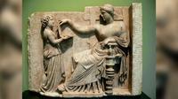 Sebuah patung dari Yunani kuno menggambarkan seorang wanita memegang alat yang sangat mirip dengan laptop di era modern.