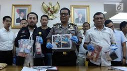 Kabid Humas Polda Metro Jaya Kombes Pol Argo Yuwono (tengah) menunjukkan barang bukti saat rilis perkara tindak pidana perjudian (pai kyu dan koprok) di Polda Metro Jaya, Jakarta, Rabu (14/3). (Liputan6.com/Arya Manggala)