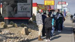 Antrean orang-orang untuk membeli senjata dan amunisi di toko senjata Ready Gunner di Orem, Utah, Minggu (10/1/2021). Penjualan amunisi dan senjata telah meningkat di Utah pada hari-hari sejak penyerbuan gedung Capitol di Washington DC pada 6 Januari 2021 lalu. (GEORGE FREY / AFP)